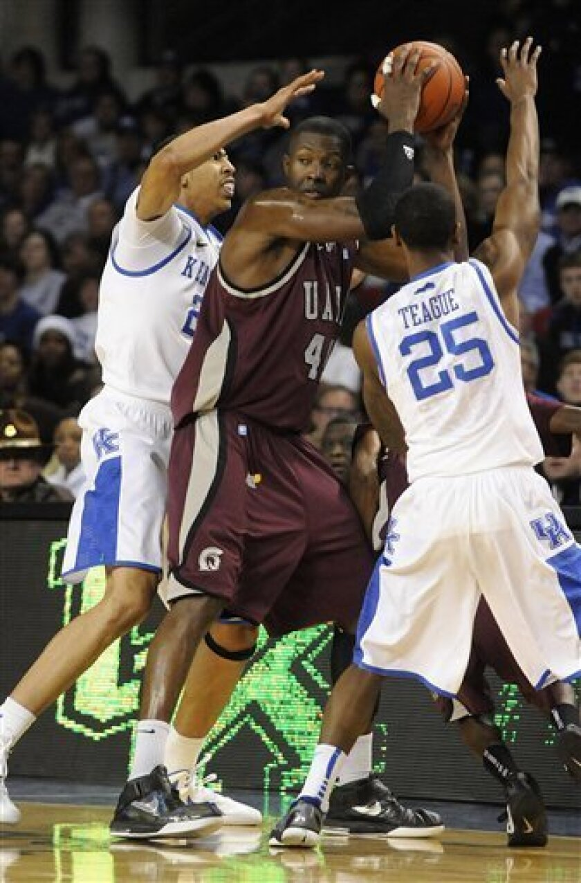 Arkansas-Little Rock's Michael Javes, center is trapped by the defense of Kentucky's Anthony Davis, left, and Marquis Teague during the first half of their NCAA college basketball game, Tuesday, Jan. 3, 2012, at Freedom Hall in Louisville, Ky. (AP Photo/Timothy D. Easley)