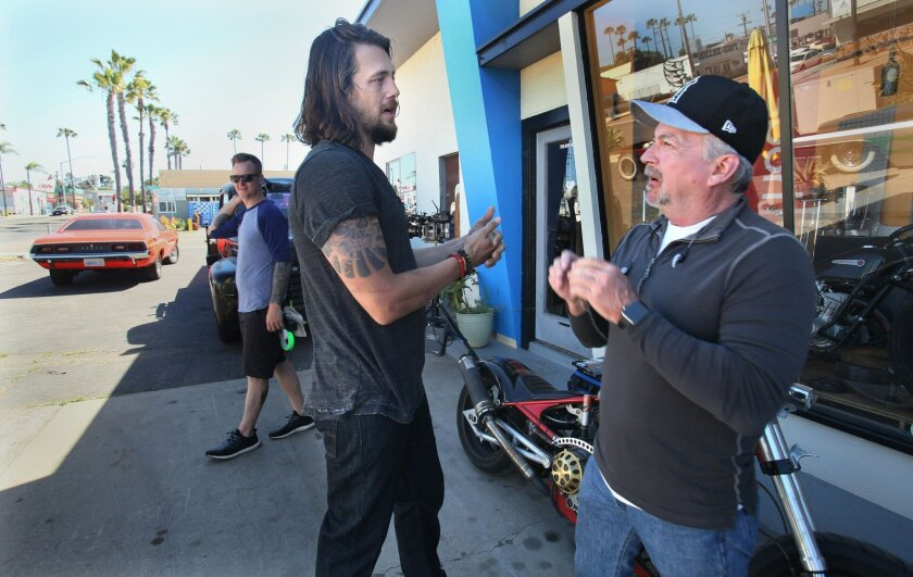 Actor Ben Robson, left, talks with executive producer Christopher Chulack between scenes at the 3M Moto Fabrications shop in Oceanside on Monday. The new TV series Animal Kingdom starring Ellen Barkin started filming Monday in Oceanside.