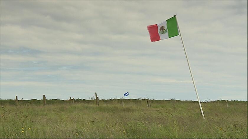 La bandera mexicana y, al fondo, la escocesa ondean en un terreno cerca del campo de golf Turnberry en Escocia, propiedad de David Milne, un opositor de Donald Trump, en esta imagen tomada de un video del miércoles 22 de junio de 2016. Milne colocó la bandera mexicana cerca de un campo de golf de Trump antes de su visita a Escocia esta semana. (STV vía AP)