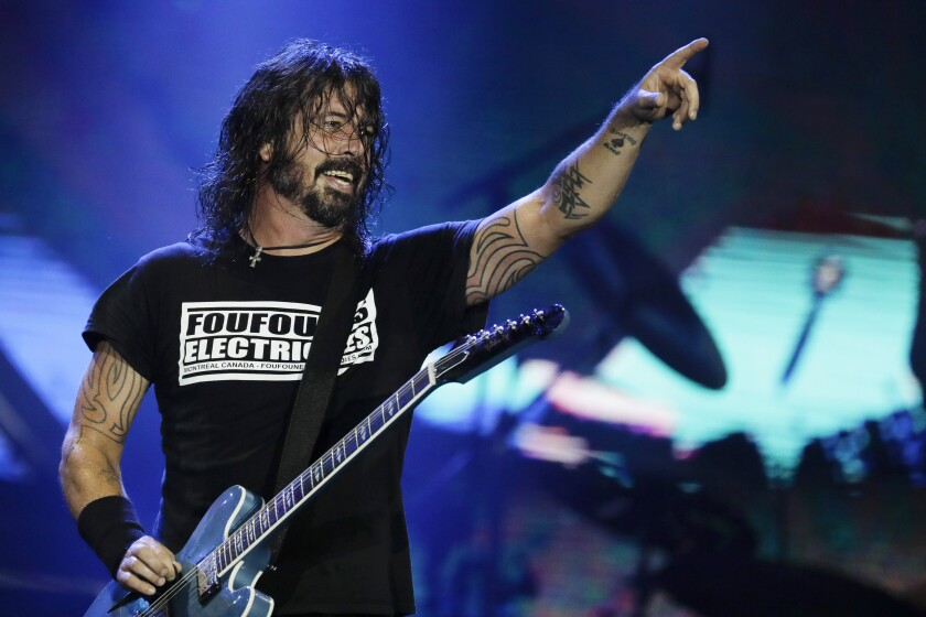Dave Grohl, with electric guitar strapped around his neck, points to the audience while performing onstage.