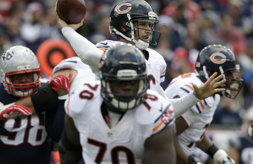 Former Bears offensive lineman Michael Ola blocks for quarterback Jay Cutler in a 2014 game against the Patriots.