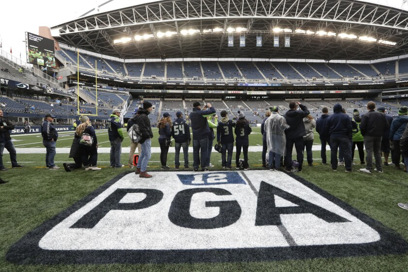 Fans stand near a logo on the turf at CenturyLink Field honoring former Seattle Seahawks owner Paul G. Allen, who died in 2018, before an NFL football game between the Seahawks and the Los Angeles Rams, Thursday, Oct. 3, 2019, in Seattle. The Seahawks were scheduled to induct Allen into the team's Ring of Honor during a pregame ceremony. (AP Photo/Elaine Thompson)
