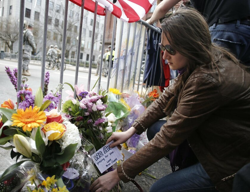A mourner places a note with flowers at a police barricade near the finish line of the Boston Marathon in Boston Tuesday, April 16, 2013.