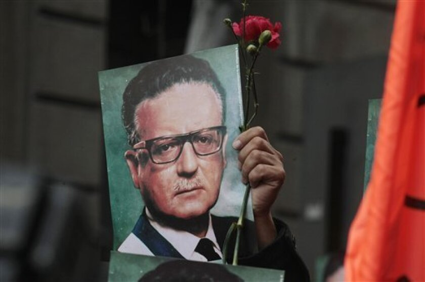 A man holds a photograph of Chile's late President Salvador Allende outside La Moneda presidential palace in Santiago, Chile, Wednesday, Sept. 11, 2013. Chile is marking the 40th anniversary of the military coup by Gen. Augusto Pinochet that overthrew Allende on Sept. 11, 1973. (AP Photo/Luis Hidalgo)