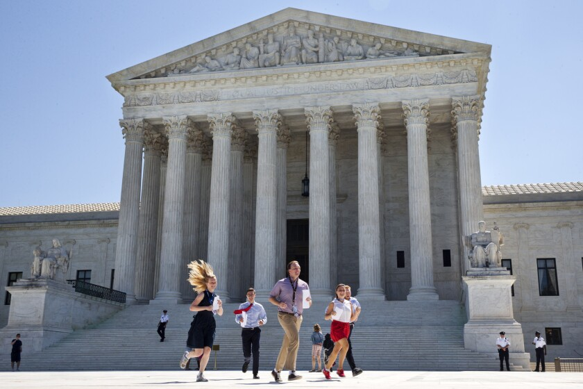 New interns run with a decision across the plaza of the Supreme Court in Washington, Monday June 29, 2015.