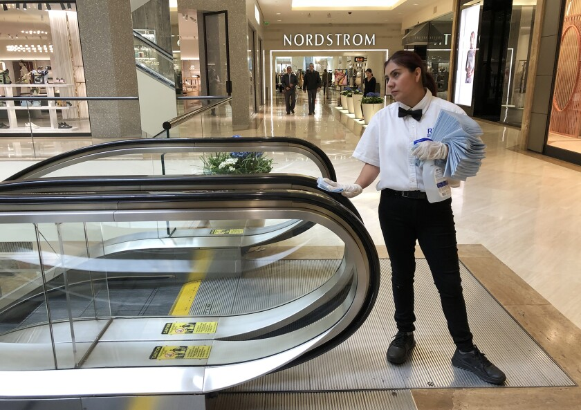 An employee at South Coast Plaza in Costa Mesa disinfects the hand rails of an escalator on March 16. The shopping center closed over a month ago.