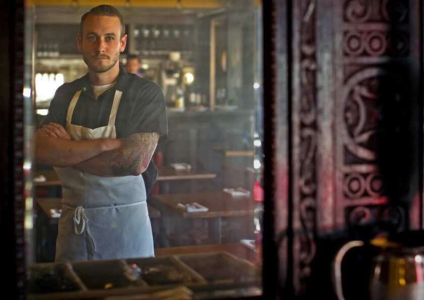 Chef Trevor Rocco, reflected in an old mirror from an antique kitchen cabinet, is the man behind the new restaurant's menu.