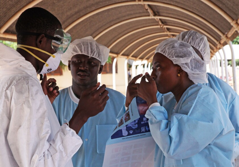 A healthcare worker briefs her colleague on the correct use of personal protection gear in Kayes, Mali, in October.