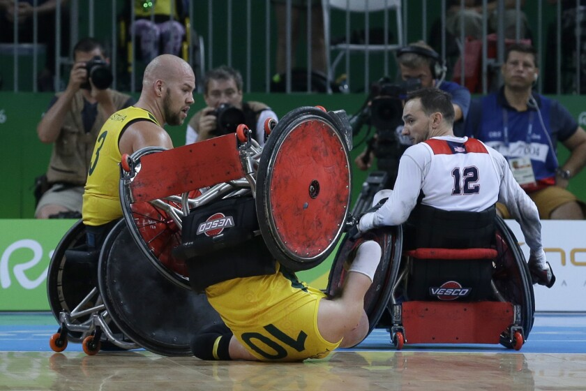 FILE - In this Sept. 18, 2016, file photo, Australia's Chris Bond falls watched by his teammate Ryley Batt, left, and United States' Chad Cohn during a mixed wheelchair rugby final match at the Paralympic Games in Rio de Janeiro, Brazil. A Tokyo Olympic test event featuring wheelchair rugby has been called off because of the threat of the spreading virus. The event was to take place on March 12-15, 2020 and original plans called for athletes from abroad. (AP Photo/Leo Correa, File)