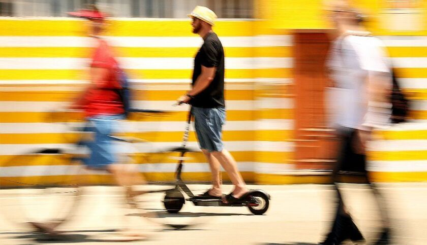 An electric scooter user rides on the Venice Beach boardwalk on Aug. 15.