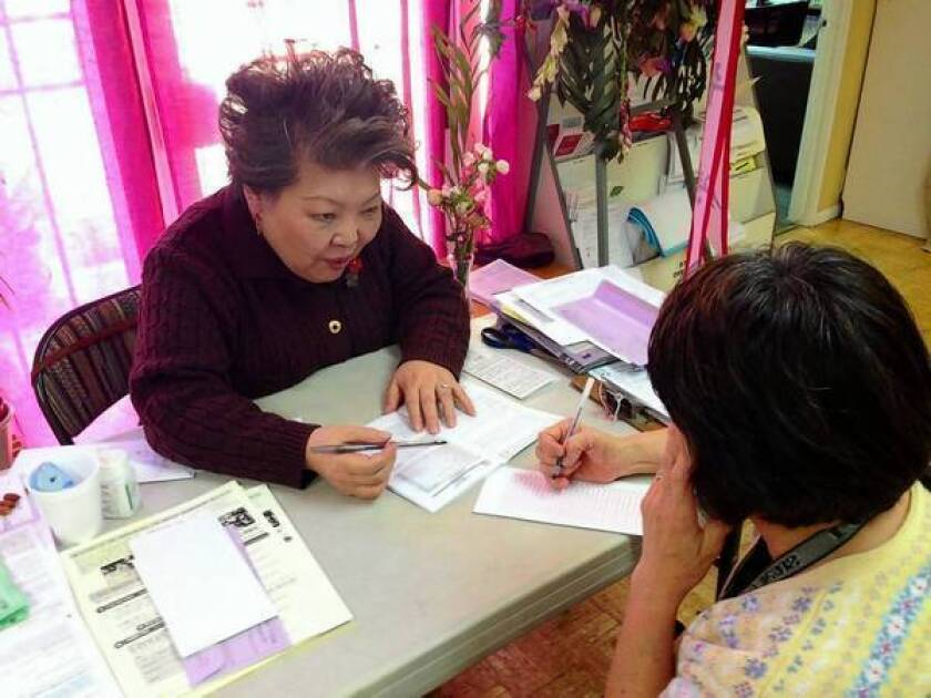 Grace Yi, a volunteer at the Korean Resource Center in Koreatown, helps a client fill out a ballot. Last year, she called 3,000 people to ask them to vote.
