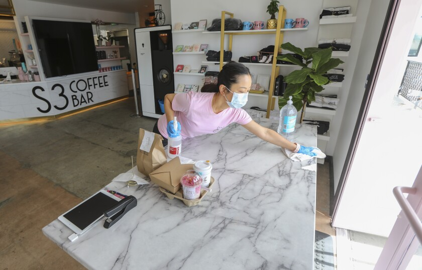 Coffee shop owner Claudia Kwong works under COVID-19 restrictions at her store called S3 Coffee Bar on Friday in San Diego. She said she will take her time reopening after the restrictions lift, ensuring her new staff has been trained appropriately to deal with the new normal way of doing business.