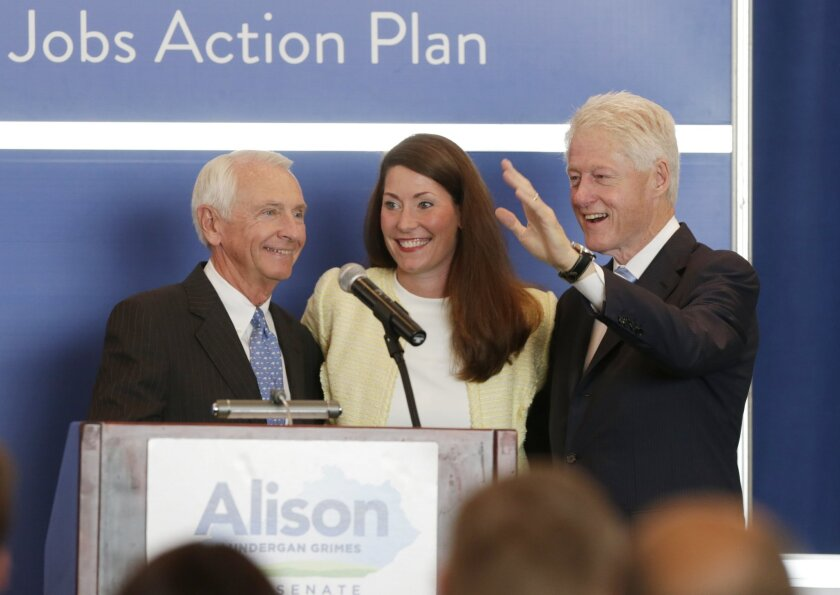 Gov. Steve Beshear, left welcomes Alison Lundergan Grimes and former President Bill Clinton to the stage during a campaign event for Grimes at the Carrick House in Lexington, Ky., Wednesday, Aug. 6, 2014. Grimes is the Democratic challenger to Sen. Mitch McConnell. (AP Photo/The Herald-Leader, Pablo Alcala)