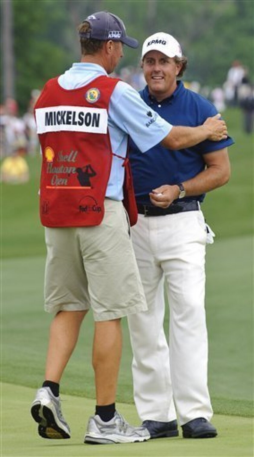 """Phil Mickelson, right, is congratulated by caddie Jim """"Bones"""" Mackay after winning the Houston Open PGA Tour golf tournament on Sunday, April 3, 2011, in Humble, Texas. Mickelson won the tournament with a 20-under par 268. (AP Photo/Dave Einsel)"""