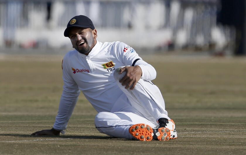 Sri Lankan skipper Dimuth Karunaratne reacts after a ball hit on his knee during the fifth day of the first cricket test match between Pakistan and Sri Lanka, in Rawalpindi, Pakistan, Sunday, Dec. 15, 2019. (AP Photo/Anjum Naveed)