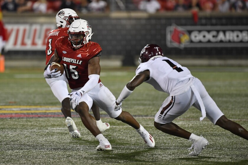 Louisville running back Jalen Mitchell (15) tries to avoid a tackle-attempt by Eastern Kentucky defensive back John Blount Jr. during the second half of an NCAA college football game in Louisville, Ky., Saturday, Sept. 11, 2021. (AP Photo/Timothy D. Easley)