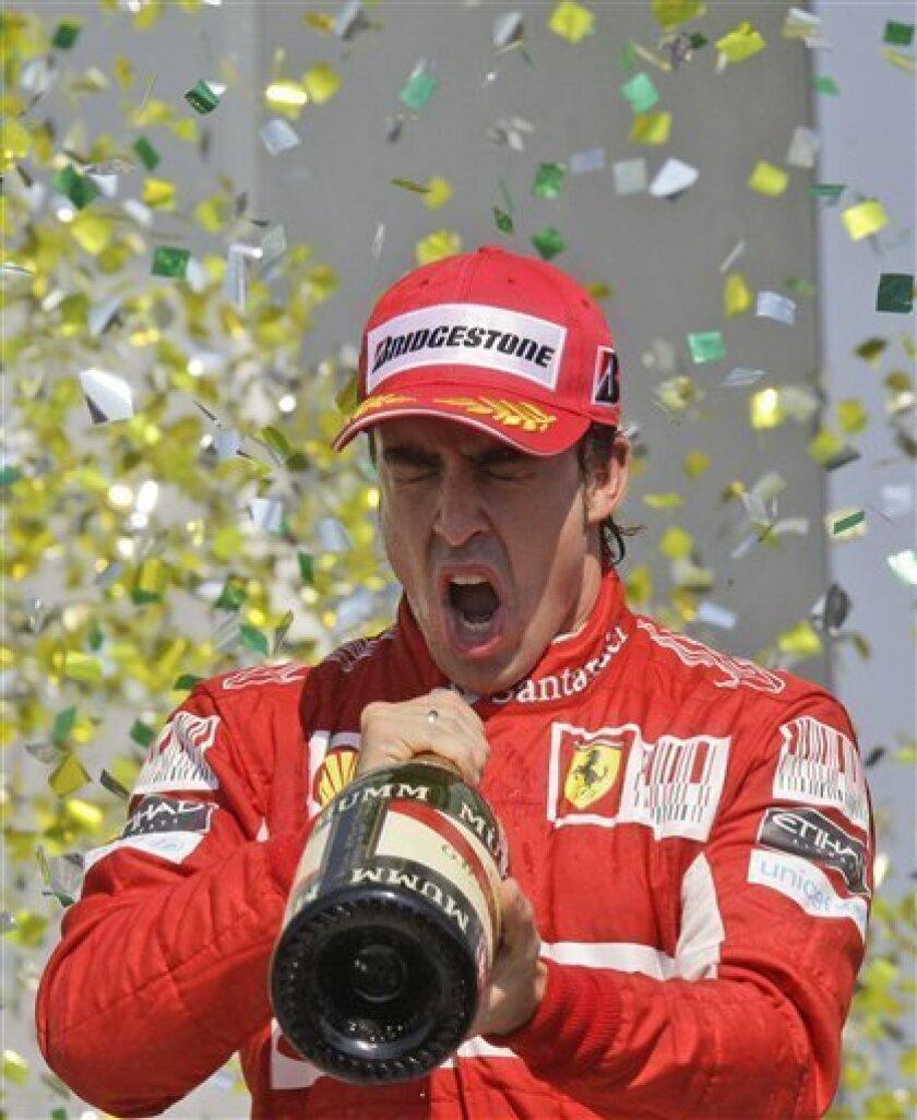 Ferrari driver Fernando Alonso of Spain celebrates on the podium after Brazil's Formula One Grand prix , at the Interlagos race track in Sao Paulo, Brazil, Sunday, Nov. 7, 2010. He arrived third. (AP Photo/Luca Bruno)