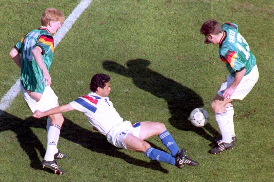 Germany team player Stefan Effenberg's shorts are tugged U.S. player Hugo Perez as German Stefan Kuntz goes for the ball