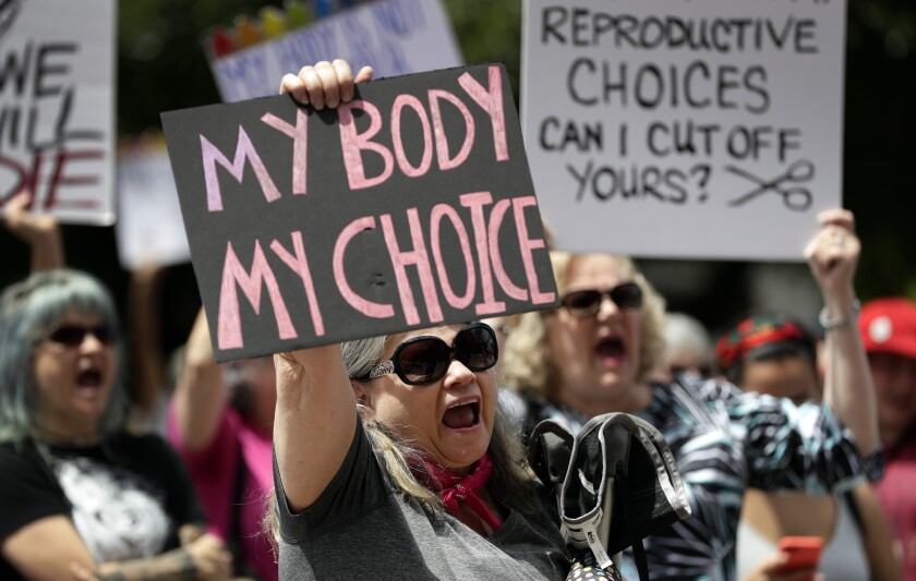 A woman holding up a sign that reads My Body My Choice is joined by other women also holding signs
