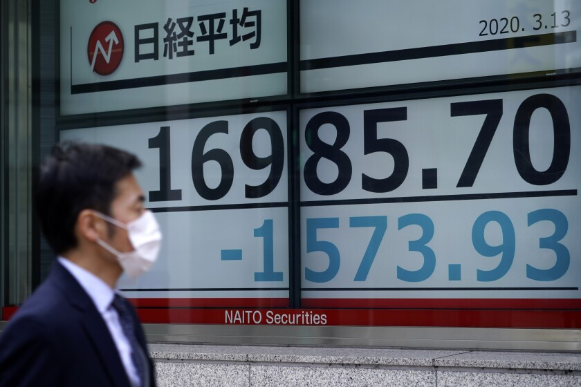 A man walks past an electronic stock board showing Japan's Nikkei 225 index at a securities firm in Tokyo Friday, March 13, 2020. Shares have plunged in Asia, with Japan's benchmark sinking 10% after Wall Street suffered its biggest drop since the Black Monday crash of 1987. (AP Photo/Eugene Hoshiko)