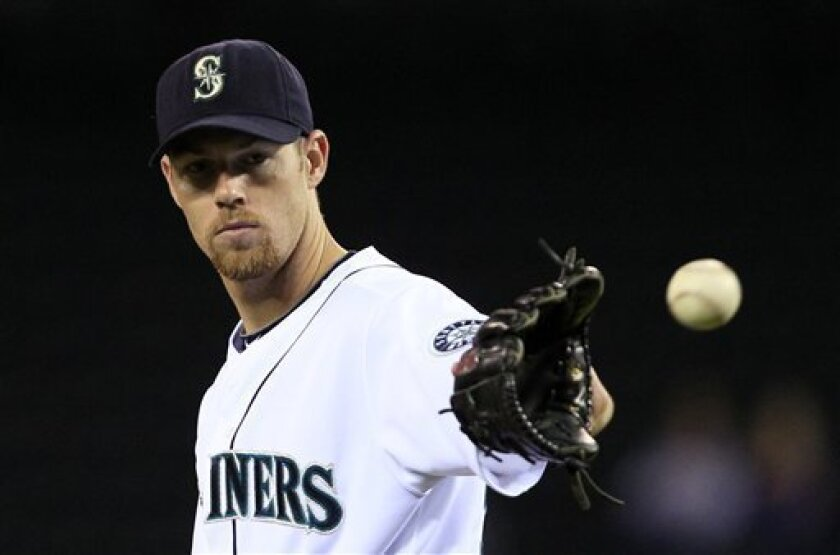 Seattle Mariners starting pitcher Doug Fister gets the ball back between pitches against the Oakland Athletics in the second inning during a baseball game Thursday, Sept. 30, 2010, in Seattle. (AP Photo/Elaine Thompson)