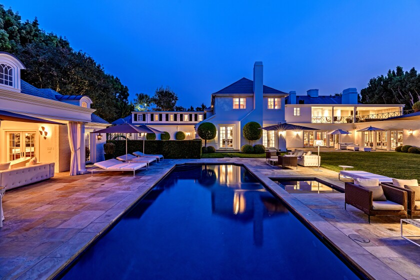 Secluded behind mature hedges and a 12-foot gate, the classic traditional-style home features dormer windows and Juliet balconies across the exterior.
