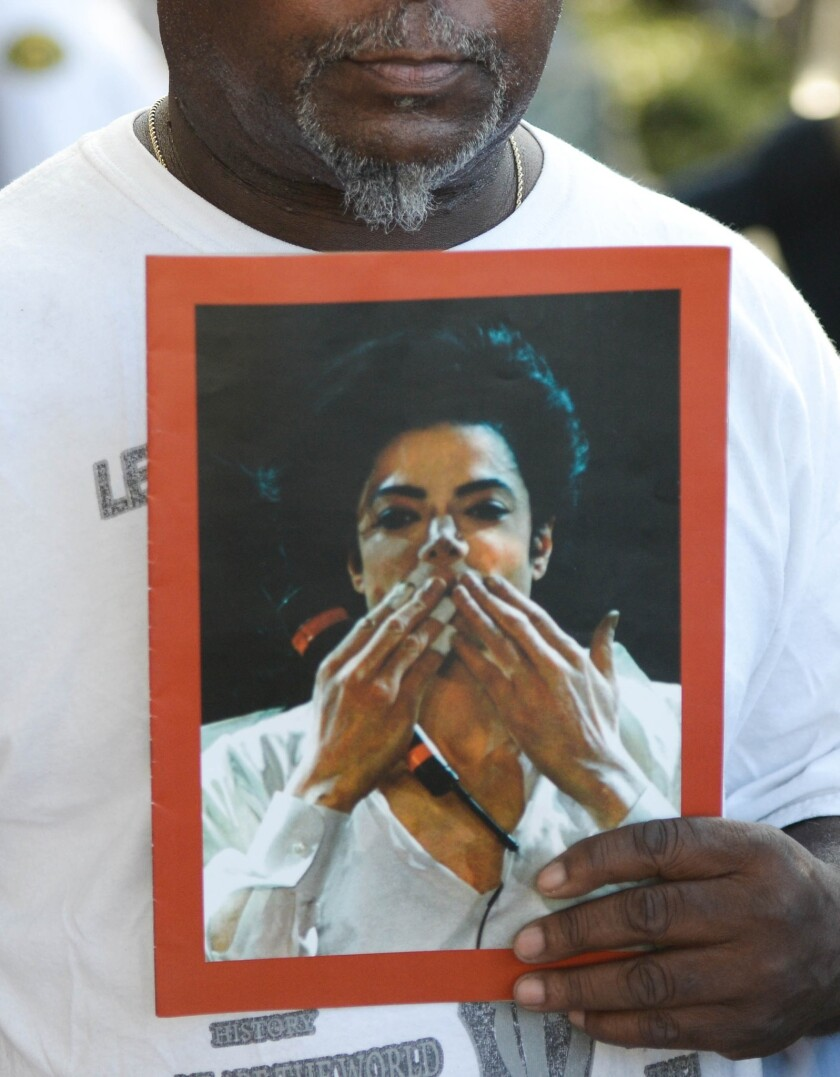 A fan holds a portrait of Michael Jackson outside court after Wednesday's verdict in the lawsuit filed by Jackson's family against AEG Live.