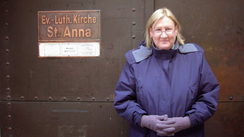 Susan Wolfe-Devol, the first woman to become a Lutheran pastor in Orange County, poses outside a church in Augsburg, Germany.