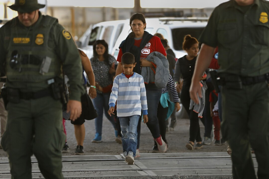 A group of about 50 men, women and children are led by U.S. Border Patrol agents to a holding area in El Paso