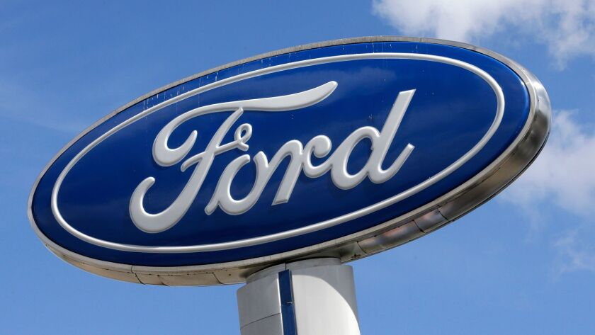FILE - This Jan. 17, 2017, file photo shows a Ford sign at an auto dealership, in Hialeah, Fla. Ford