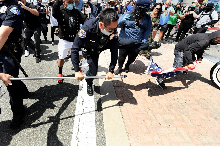 A police officer tries to intervene as a young man takes an American flag from a demonstrator