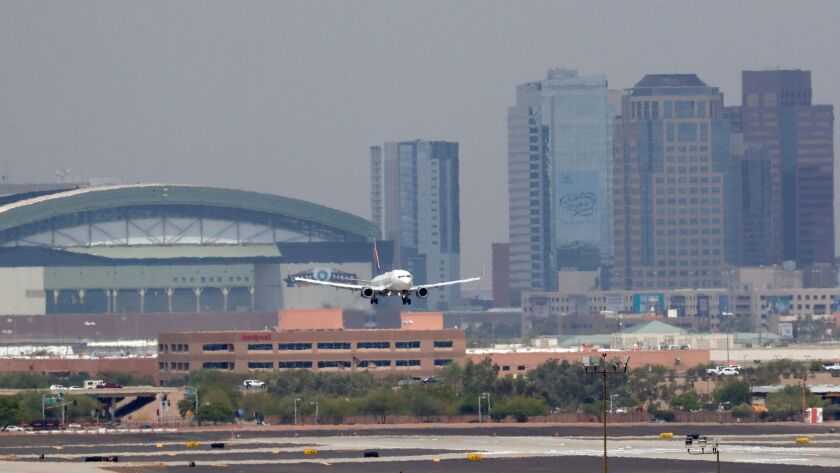 Heat waves ripple across the tarmac at Sky Harbor International Airport as downtown Phoenix stands i