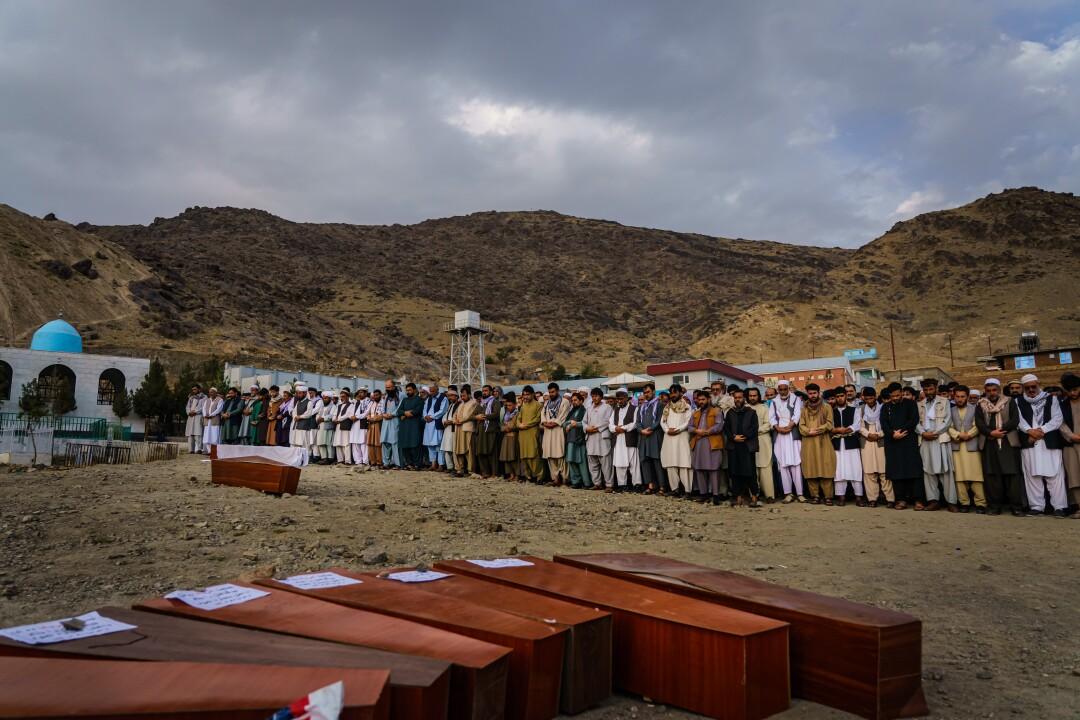 A crowd prays near caskets laid on the ground