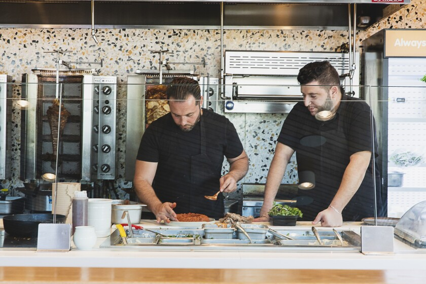 Simsim executive chef Ibrahim AlSharief, left, prepares a plate of muhammara, a roated red pepper spread at the new Carmel Mountain Ranch restaurant.