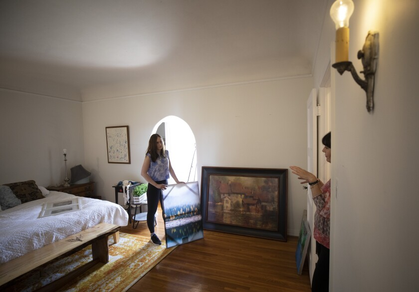 Two women talk in an apartment. One of them holds a piece of art for a wall.