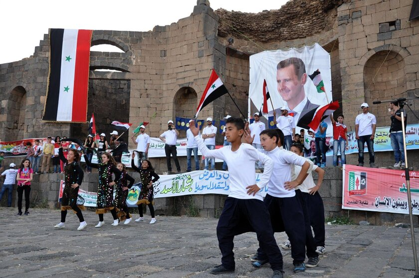 In this Saturday, May 31, 2014, photo released by the Syrian official news agency SANA, supporters of Syrian President Bashar Assad hold his portraits and wave Syrian flags during a demonstration in support of his candidacy for presidential election in Sweida town, southern Syria. The country holds its first multi-candidate presidential election in nearly half a century on Tuesday, June 3, but voting will occur only in government-held territory. Hundreds of thousands of people live in areas that are either contested, held by rebels or blockaded by pro-government forces. (AP Photo/SANA)