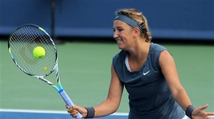 Victoria Azarenka, of Belarus, returns a volley to Vania King, of the United States, during a match at the Western & Southern Open tennis tournament on Tuesday, Aug. 13, 2013, in Mason, Ohio. (AP Photo/Tom Uhlman)