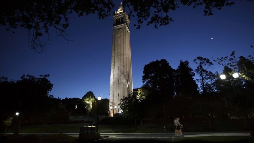 BERKELEY, CA - SEPTEMBER 09, 2015: Early morning joggers pass the Campanile on the campus of the Uni