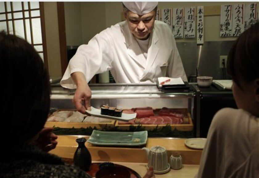 A chef serves fatty tuna and pickles rolls for customers at a sushi restaurant in Tokyo Tuesday, April 5, 2011. The government set its first radiation safety standards for fish Tuesday after Japan's tsunami-ravaged nuclear plant reported radioactive contamination in nearby seawater measuring at several million times the legal limit. (AP Photo/Shuji Kajiyama)