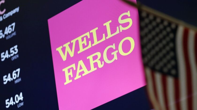 The logo for Wells Fargo appears above a trading post on the floor of the New York Stock Exchange.