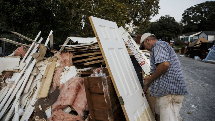 Lino Saldana salvages doorknobs to save money to rebuild his flooded home in the Kashmere Gardens neighborhood of Houston.