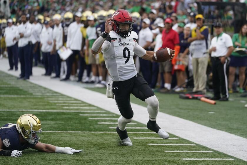 Cincinnati quarterback Desmond Ridder (9) runs in for a touchdown against Notre Dame's JD Bertrand (27) during the second half of an NCAA college football game, Saturday, Oct. 2, 2021, in South Bend, Ind. Cincinnati won 24-13. (AP Photo/Darron Cummings)