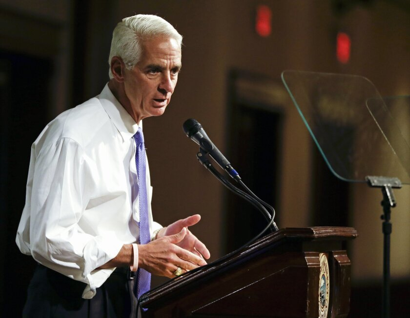 """FILE -This May 21, 2014 file photo shows Florida Democratic gubernatorial candidate Charlie Crist campaigning in Orlando, Fla. Recently, campaigning in Miami's Little Havana, Crist stood before a crowd and said what few politicians have in decades of scrounging for votes in the Cuban-American neighborhood: end the trade embargo against Cuba. """"If you really care about people on the island, we need to get rid of the embargo and let freedom reign,"""" he said, shouting above a small band of protesters who responded with chants of """"Shame on you!"""" Crist's supporters cheered louder. (AP Photo/John Raoux, File)"""