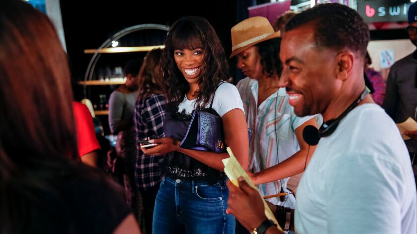 Actresse Yvonne Orji, center, jokes with executive producer Prentice Penny on location at the W Holl