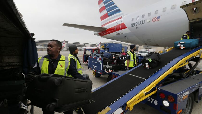 Workers unload baggage from an American Airlines plane at Los Angeles International Airport. The nation's biggest carriers had the highest rating last year for airline quality in the 27-year history of a Wichita State University study.