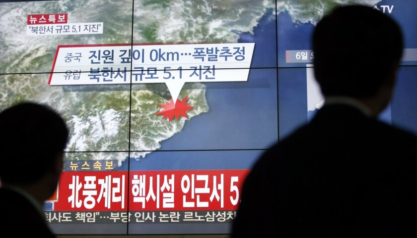 """FILE - In this Wednesday, Jan. 6, 2016, file photo, people walk by a screen showing the news reporting about an earthquake near North Korea's nuclear facility, in Seoul, South Korea. South Korean officials detected an """"artificial earthquake"""" near North Korea's main nuclear test site Wednesday, a st"""