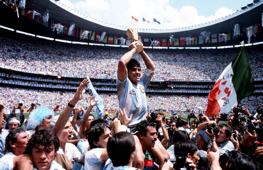 Argentina captain Diego Maradona holds the World Cup trophy while being carried on his teammates' shoulders.