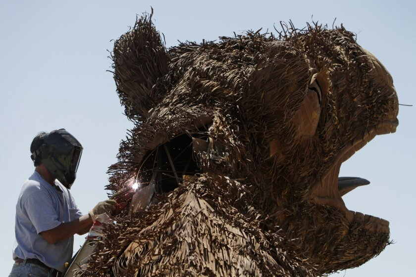 Sculptor Ricardo Breceda welds as he works on his sculpture of a giant sloth in the Borrego desert on Friday.