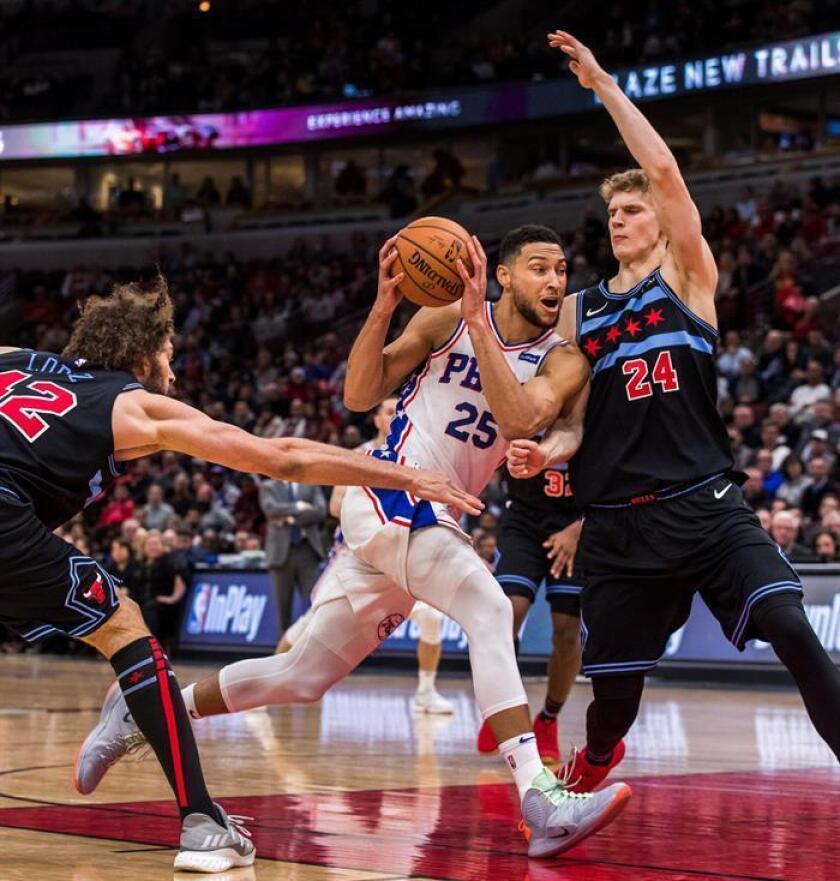 Ben Simmons (c) de Philadelphia 76ers en acción ante la defensa de Robin Lopez (izq) y Lauri Markkanen (dcha) de Chicago Bulls durante un partido de la NBA entre los Philadelphia 76ers y Chicago Bull disputado en el United Center de Chicago (EE.UU.). EFE