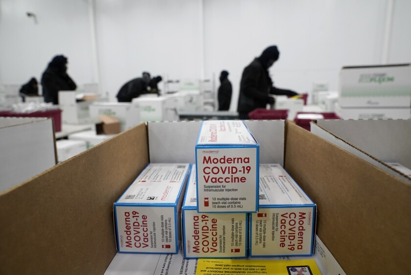 "Boxes labeled ""Moderna COVID-19 vaccine"" are stacked at a distribution center."